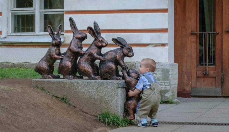 Niño formado atrás de unos conejos como estatua