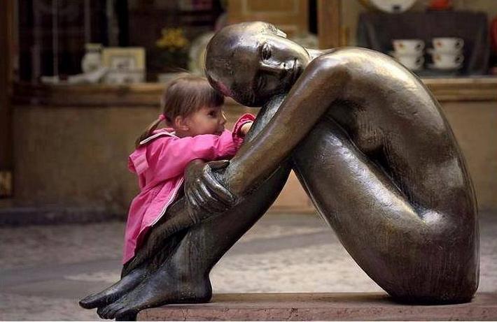 NIña contándole un secreto a una estatua