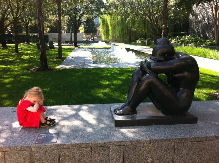 Niña sentada frente a una estatua con las manos en la cabeza
