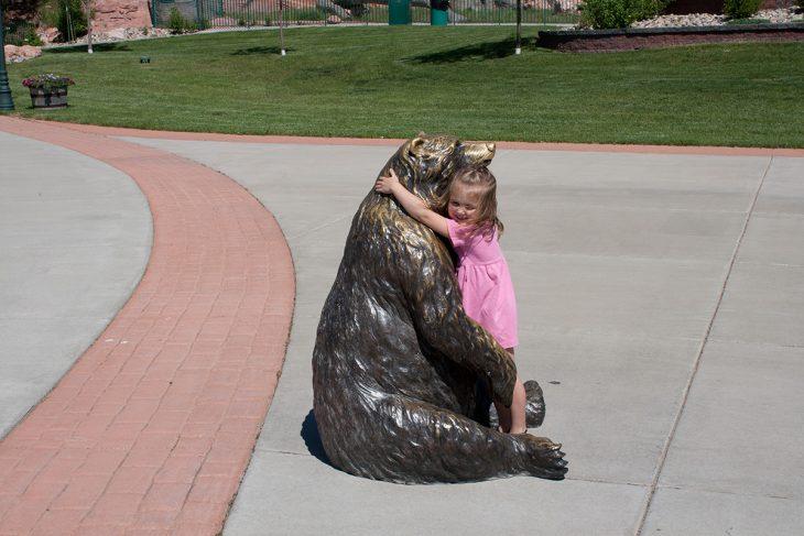 Niña abrazando a una estatua en forma de oso