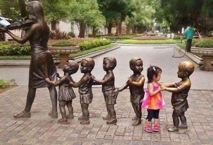 niña intentando jugar con varias estatuas de niños