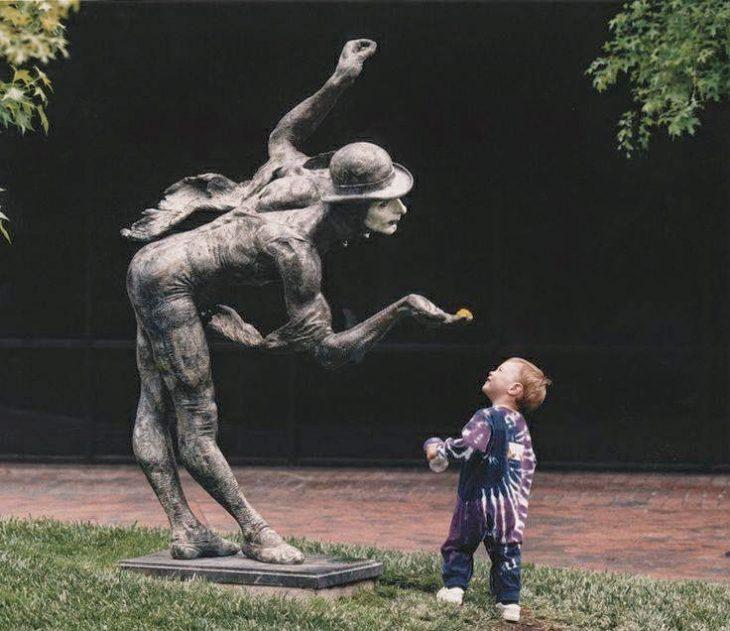 Niño viendo con curiosidad una estatua