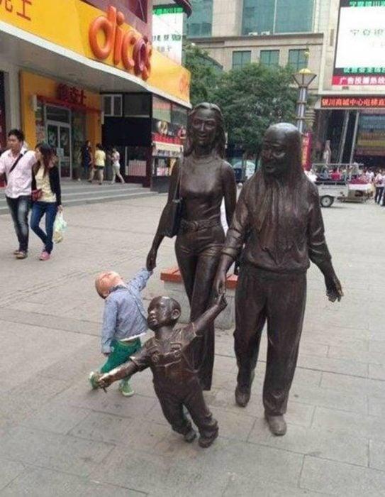 Niño tomando de la mano a una estatua que piensa que es su mamá