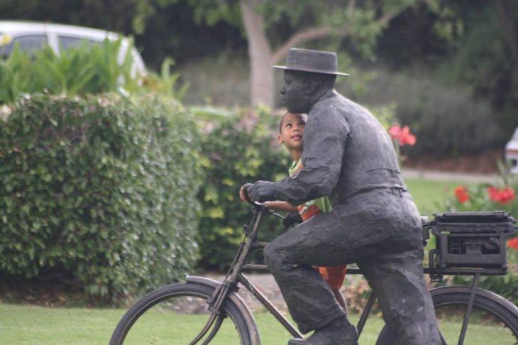 Niño sujetándose de la bici de un señor que es una estatua