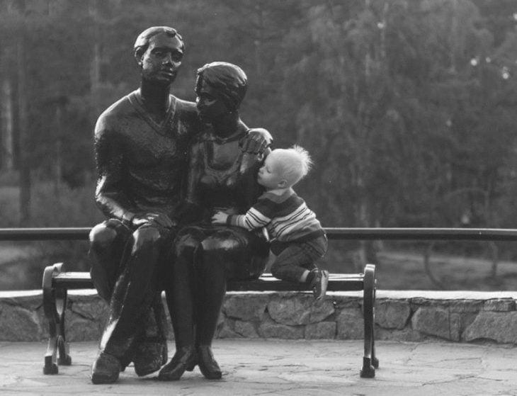 Niño abrazando a unas estatuas