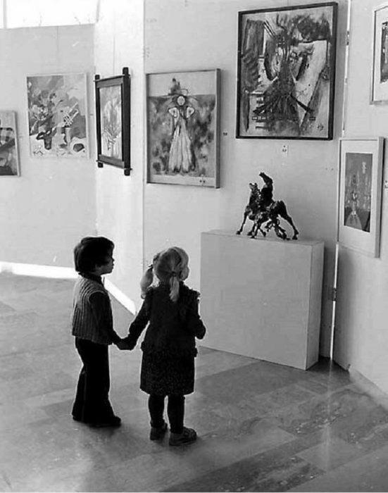 Niños observando muy atentamente a unas estatuas en un museo