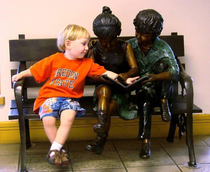 Niño intentando mostrar algo en un libro a unas estatuas