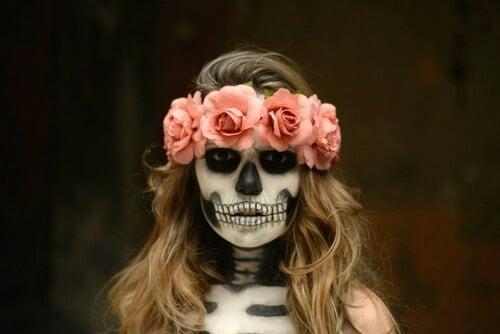 Chica con maquillaje para halloween de catrina con flores