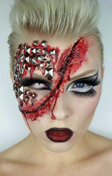 Chica con maquillaje para halloween con una herida en la mitad del rostro y estoperoles