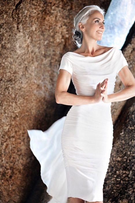 Mujer modelo de 59 años de edad usando un vestido de color blanco mientras está parada sobre las rocas