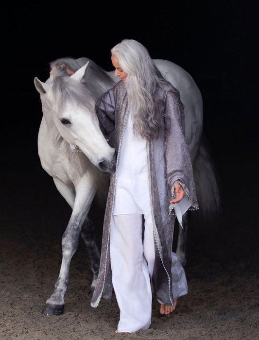 Modelo de 59 años de edad posando en una sesión de fotos junto a un caballo
