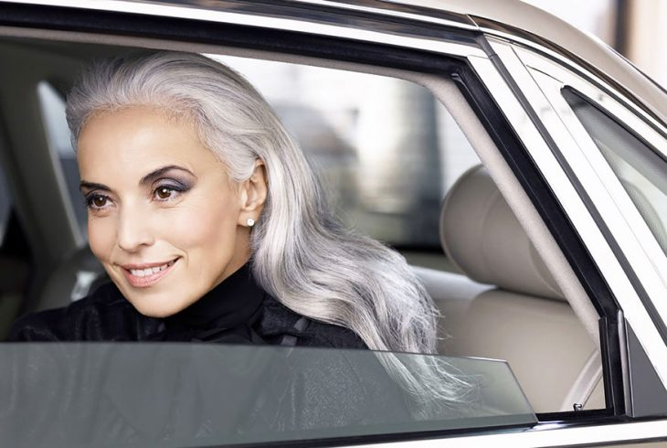 Modelo de 59 años de edad sobre un carro sonriendo durante una sesión de fotos