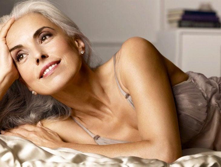 Modelo de 59 años de edad recostada en una cama sonriendo