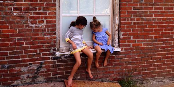 niñas sentadas en una ventana
