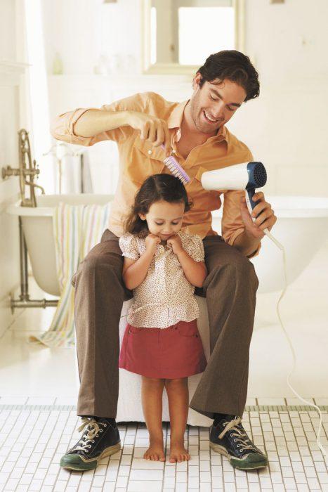 padre peinando a hija