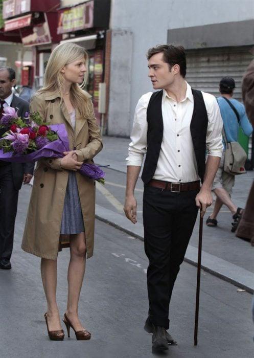 Escena de la serie gossip girls chuck y su novia caminando por la calle