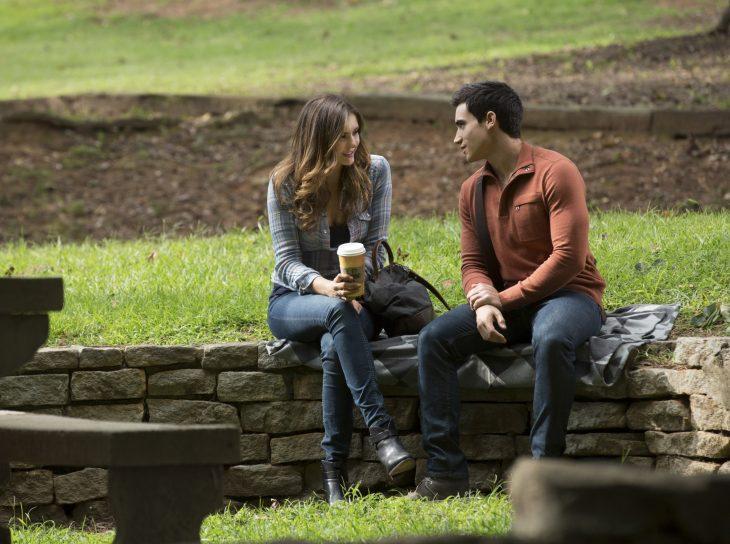 pareja de novios sentados en el parque conversando mientras toman café