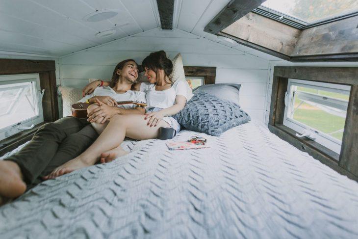 Pareja de novios recostados en una cama mirándose el uno al otro