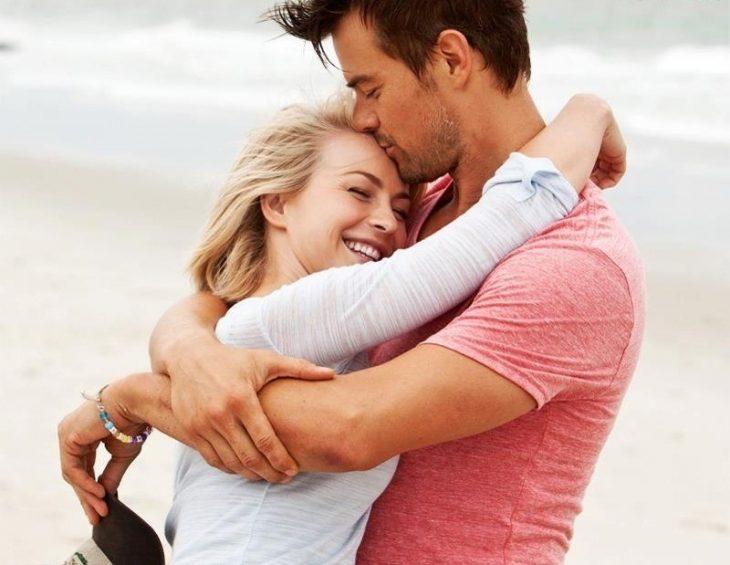 Pareja de novios abrazados sonriendo mientras están en la playa