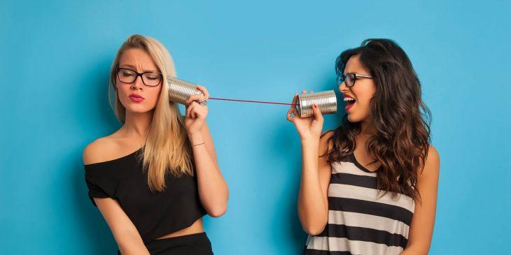 Chica hablando con otra a través de dos latas con un cable