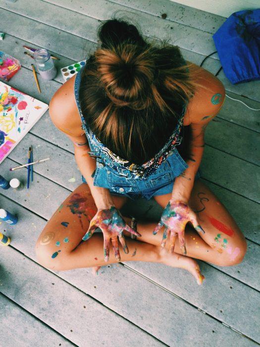 Chica sentada en el suelo con las manos llenas de pintura