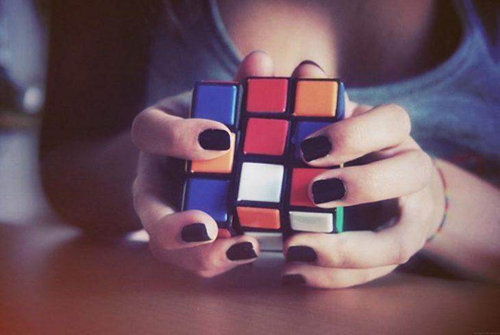 Chica jugando con un cubo de rubik