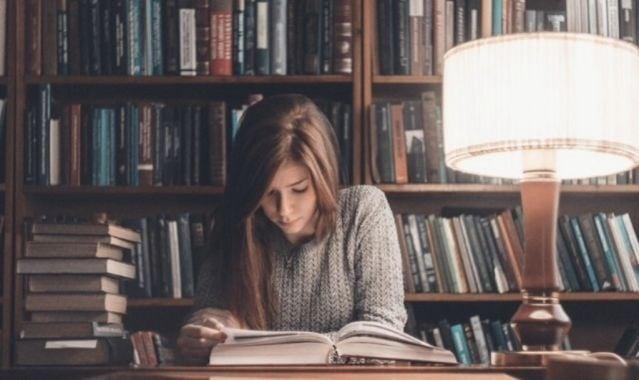 Chica en una biblioteca estudiando