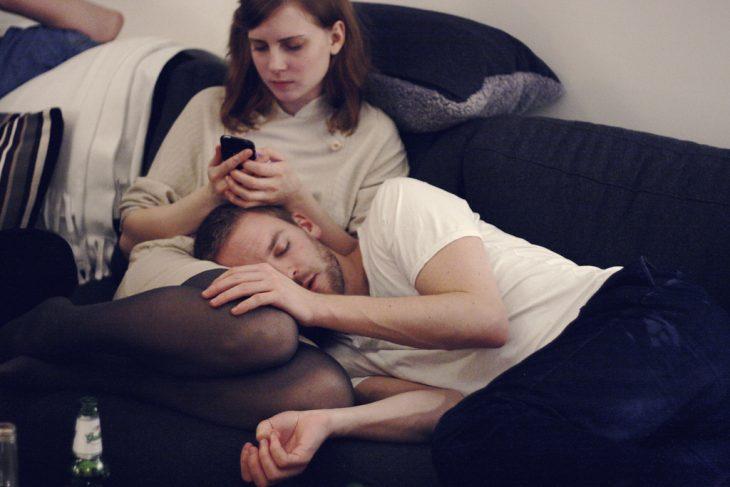Pareja descansando, él dormido y ella en el celular