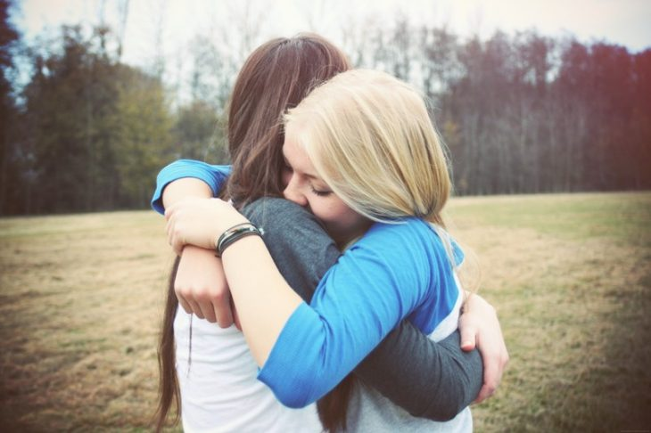 Amigas abrazadas con un campo de fondo