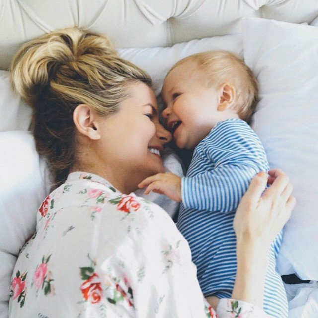 mamá junto a su bebé sonriendo mientras están recostados en la cama