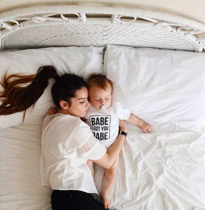 Mamá durmiendo junto a su bebé en la cama