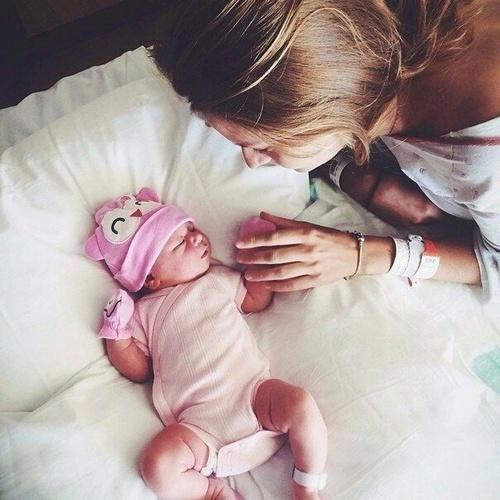 Madre tomando la mano de su bebé que esta recostado en la cama