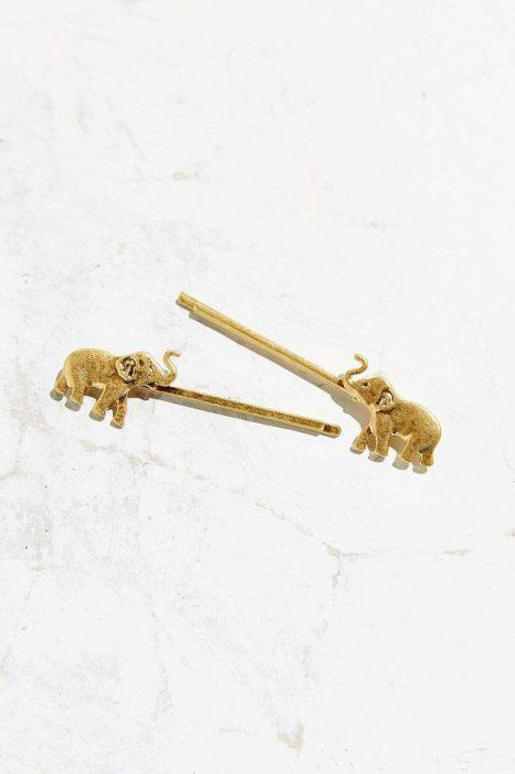 brocehs de color dorado con un elefante al final de ellos