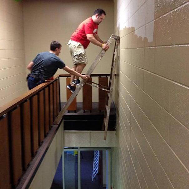 Hombre sosteniendo una escalera en un vacio mientras el otro pinta