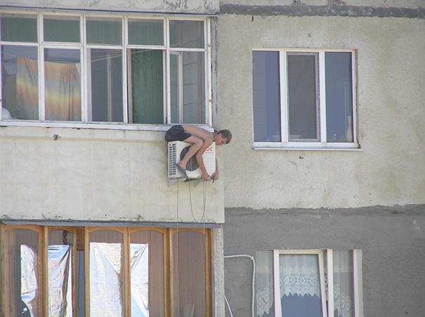 Chico sobre un aire acondicionado tratando de arreglarlo