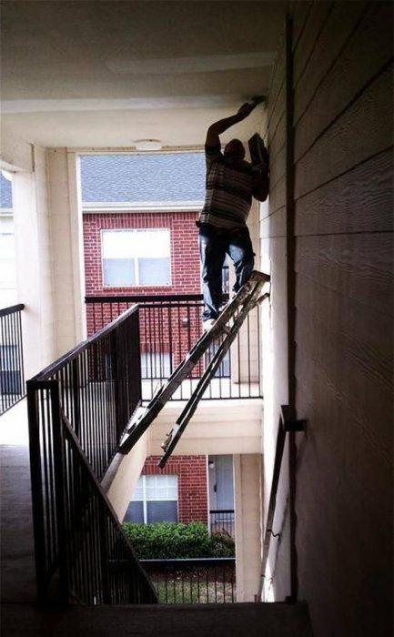 Hombre sobre una escalera colocada al vacio intentando cambiar un foco