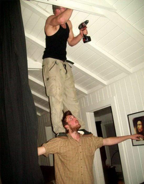 hombre parado sobre otro perforando una pared