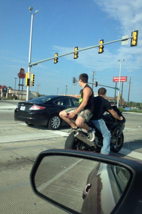 Hombre sentado en la parte de atrás de una motocicleta, pero viendo al frente