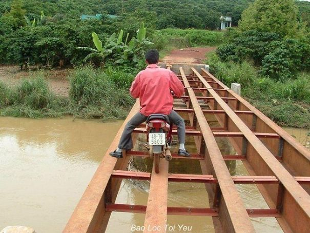 Hombre cruzando un puente con su motocicleta