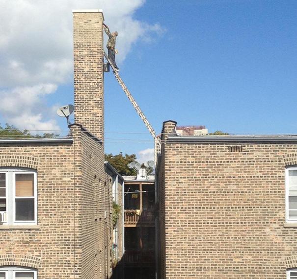 Hombre pintando a fachada de una casa a otra mientras está sobre una escalera