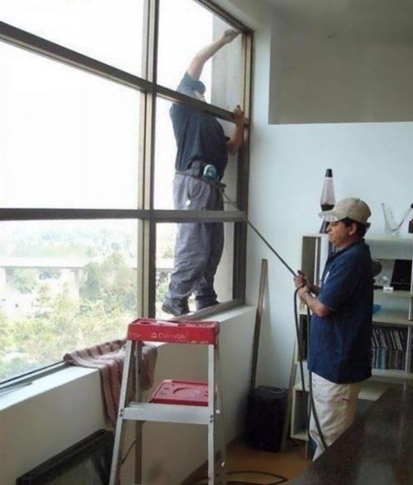 Hombre sujetando a otro con una cuerda mientras está afuera de una ventana
