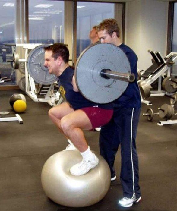 Hombre cargando unas pesas mientras está sobre una pelota de yoga