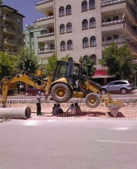 tractor colocado para que le de sombra a unos hombres