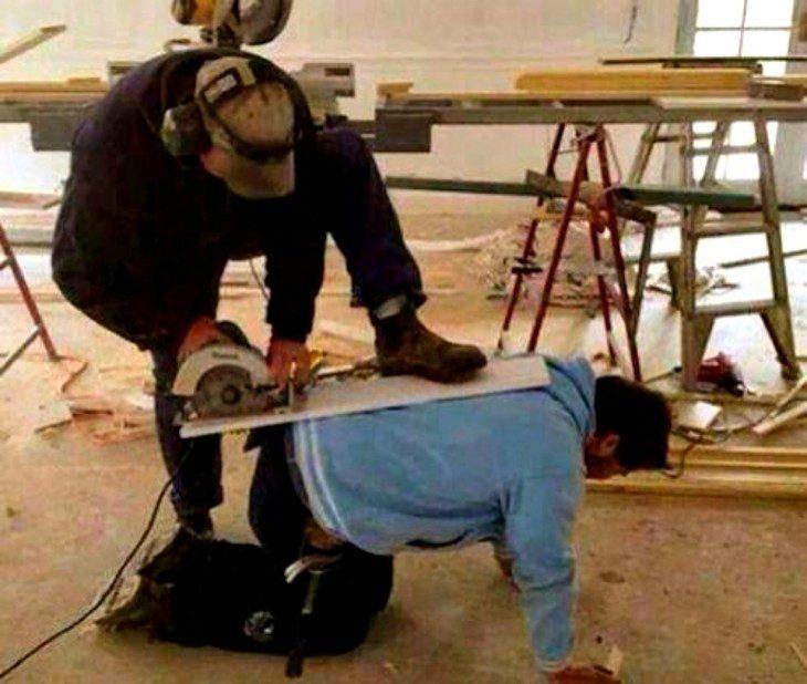 Hombre sirviendo como soporte para que otro pueda cortar una tabla con una cortadora