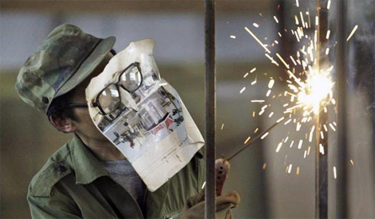 Hombre con un trozo de periódico sobre la cara mientras está soldando
