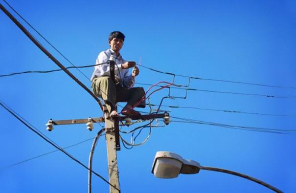 Hombre sobre un poste de luz arreglando los cables