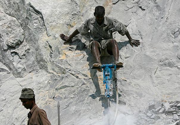 Hombre con una perforadora en una piedra sosteniéndola con los pies