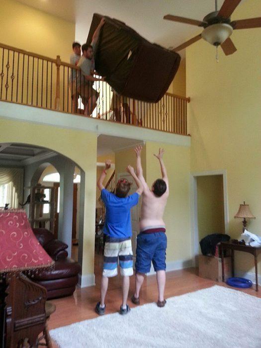 Hombres intentando atrapar un sofá