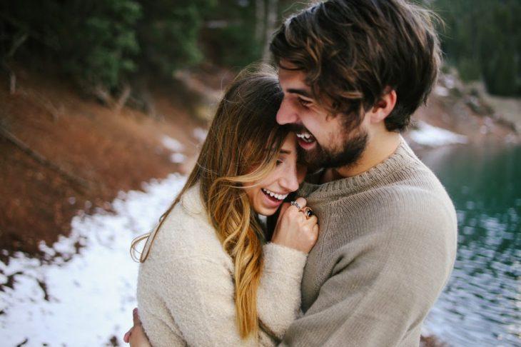 Pareja de novios abrazados tiendo mientras están en la nieve
