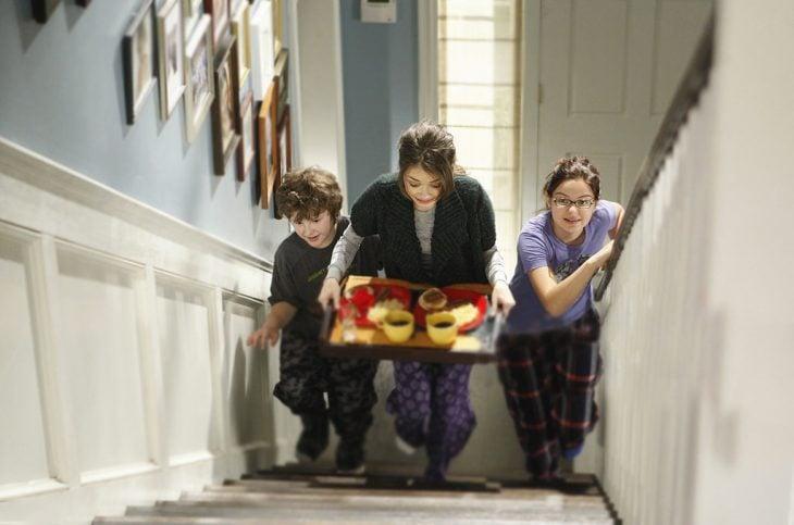 Escena de la serie modern family hermanos corriendo por las escaleras